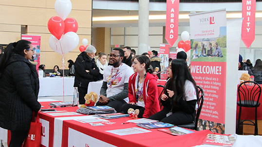 York students talking to passerby during fair in Vari Hall