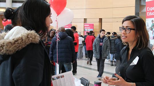Volunteers speaking to students in vari hall at open house