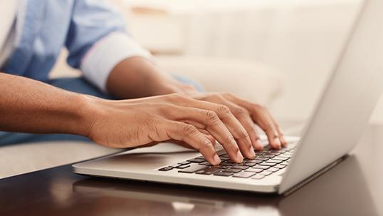 hands hovering over laptop keyboard