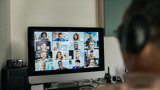 desktop computer with full screen video conferencing open