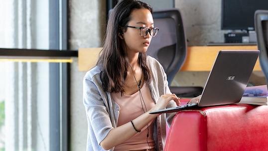 girl on laptop wearing headphones