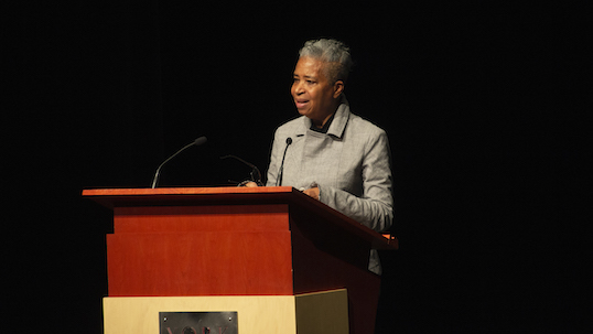 Author and poet Dionne Brand stands at podium while giving a lecture at York University