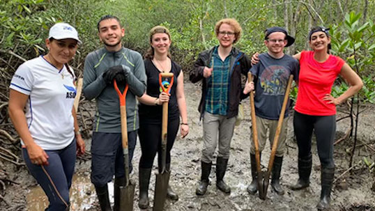 Six students pose for happy photo while holding shovels in muddy outdoor setting