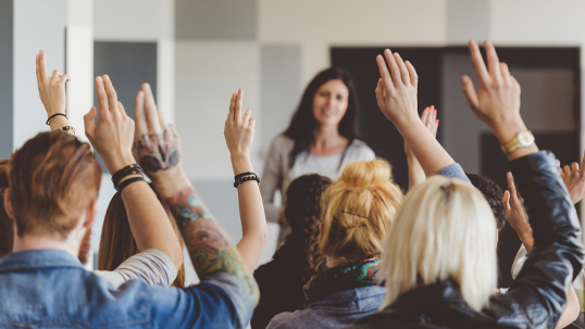 Woman stands in front of class during seminar while students raise hands