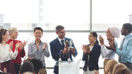 Multicultural group of men and women applaud man in suit and tie accepting an award