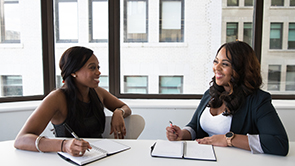Two professional black women have a meeting in a boardroom while taking notes.