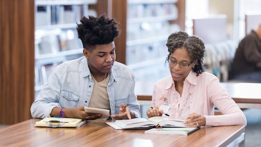 An African American teacher helps her student before class