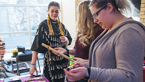 Indigenous student shows other students some Indigenous artifacts.