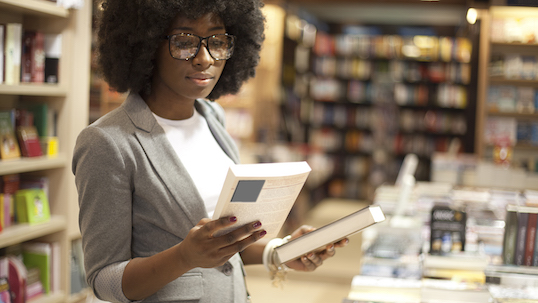 Black woman at bookstore holding books in her hands before making a purchase