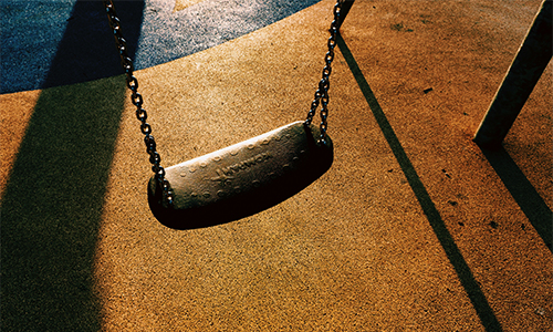 Overhead view of an empty swing on a playground during sunset