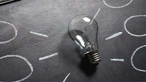 Abstract photo featuring a lightbulb on a chalkboard.