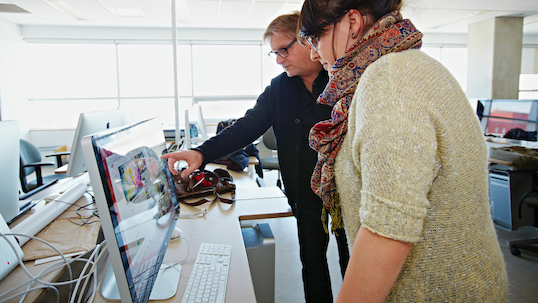 Man points at computer monitor while standing next to a woman in a computer lab at York