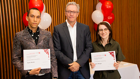 Male instructor stands between male and female students holding prize certificates while smiling for a photo