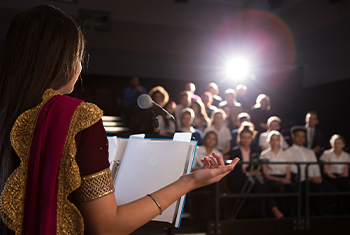 Young woman stands at podium to read a presentation in front of an audience