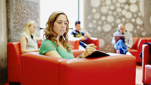 a woman sits and writes in her notebook while the other people are blurred in the background