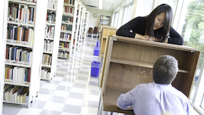 a woman rests her arms over a desk in the library while another student sits
