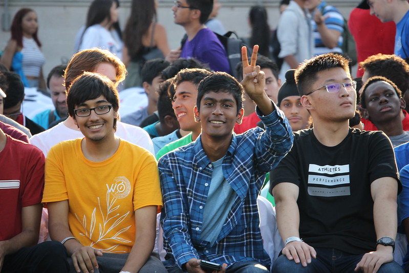 Three seated students smiling and laughing at York Orientation Day.