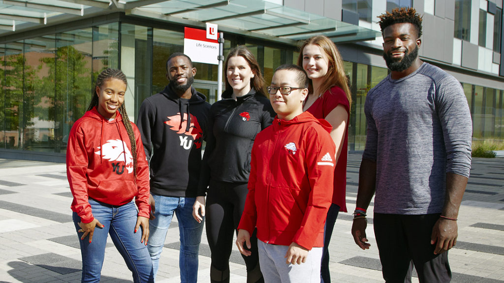 Six students in York Lions attire outside the Life Sciences building
