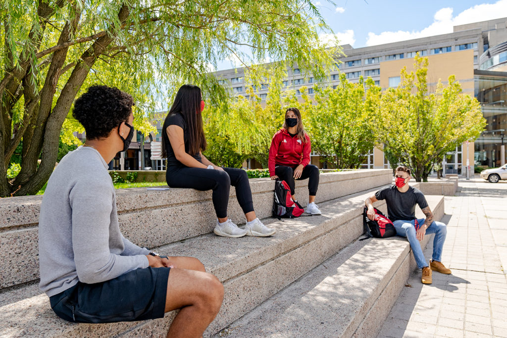 Four socially distanced students wear masks while siting on the steps in the York University Commons on a sunny day.