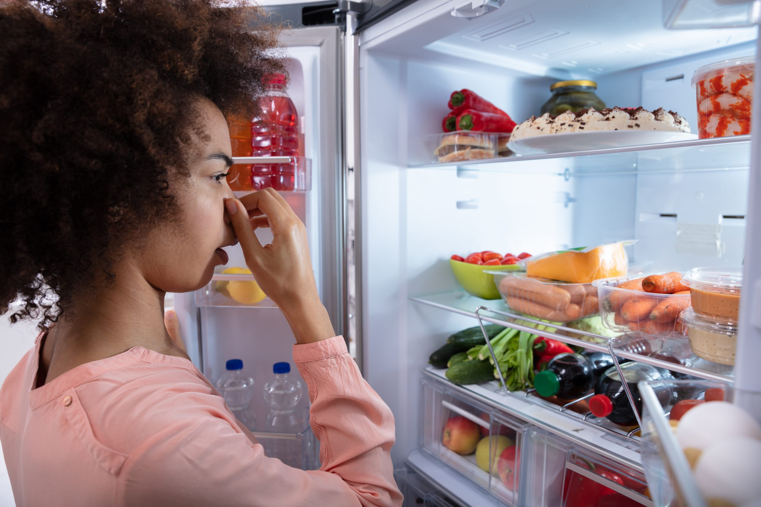 person looking into fridge holding nose at smell