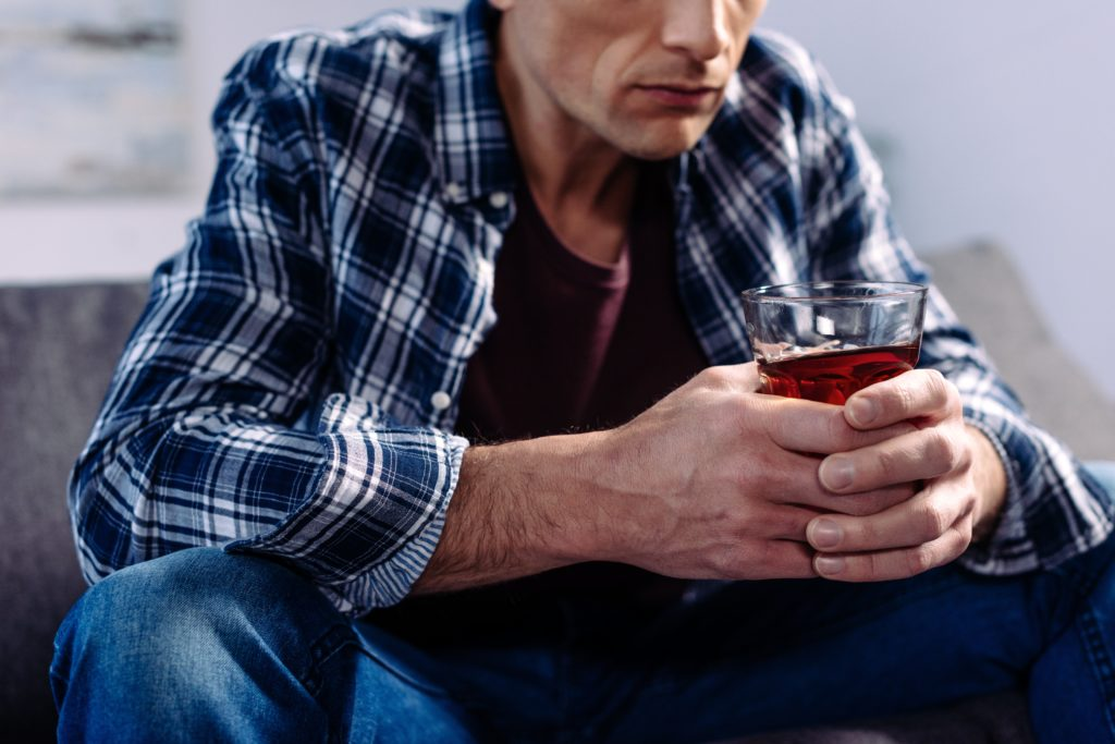 Man drinking alcohol on sofa