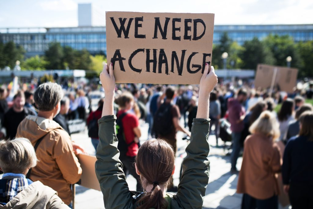 Rally with sign: We Need a Change