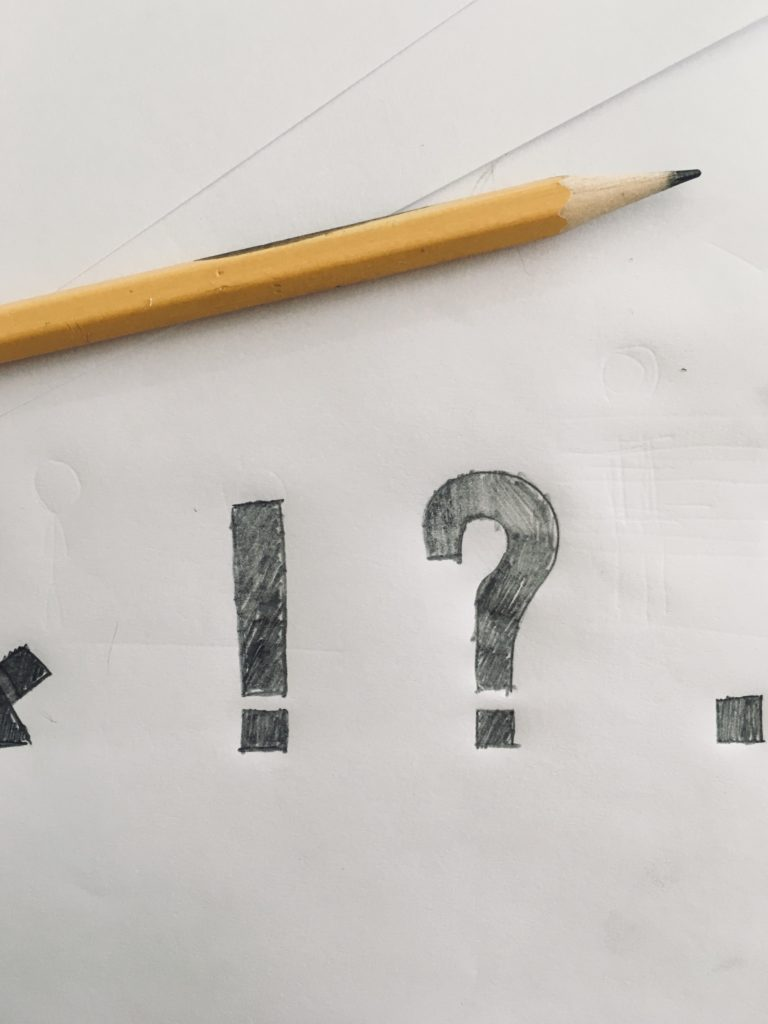 Pencil on white paper with question mark drawn.