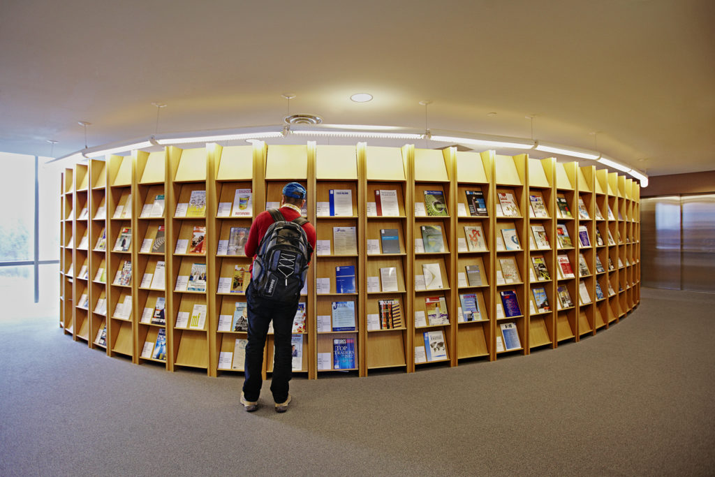 Student standing in front of magazine shelf at Bronfman library