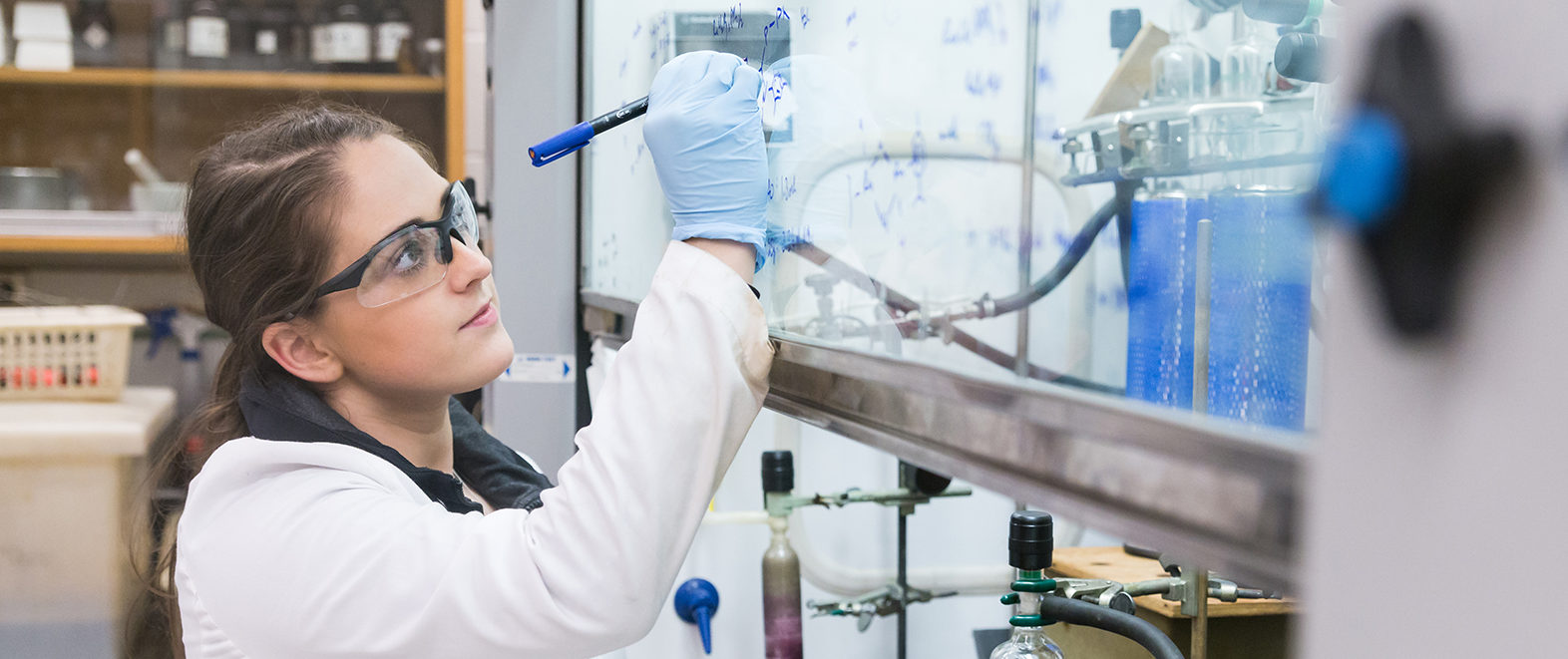 Female student writing on a glass in lab.