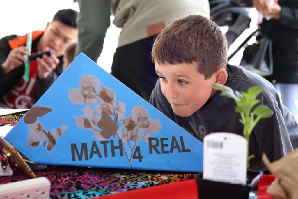 Young student at Math4Real event looking at a diagram