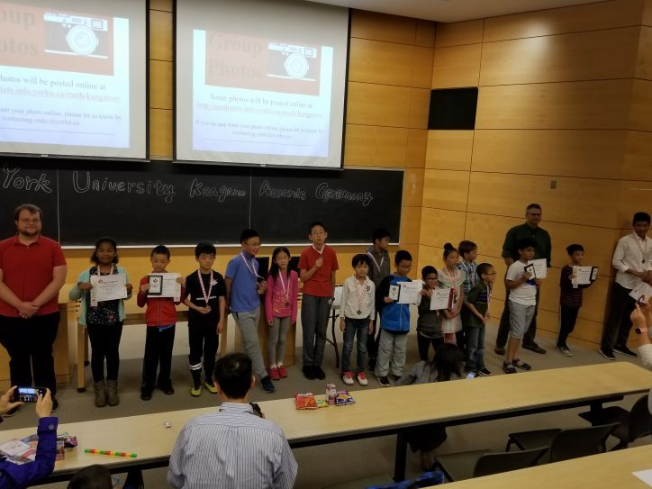 Students standing at the front of the classroom holding awards at Math Kangaroo