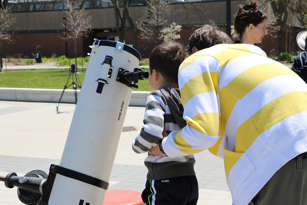 Parent holding child looking into large microscope.