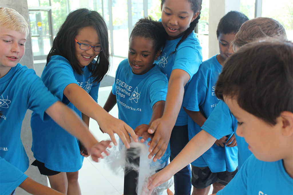 Group of kids touching science experiment.
