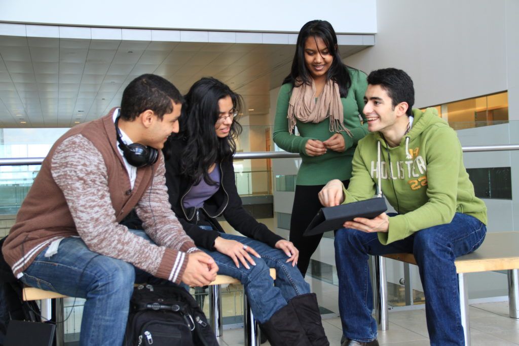 Four students sitting and talking on campus