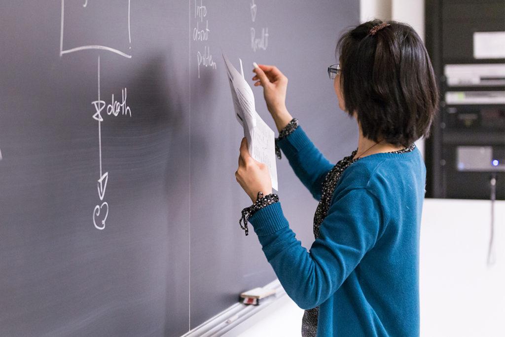 Professor writing on chalkboard.