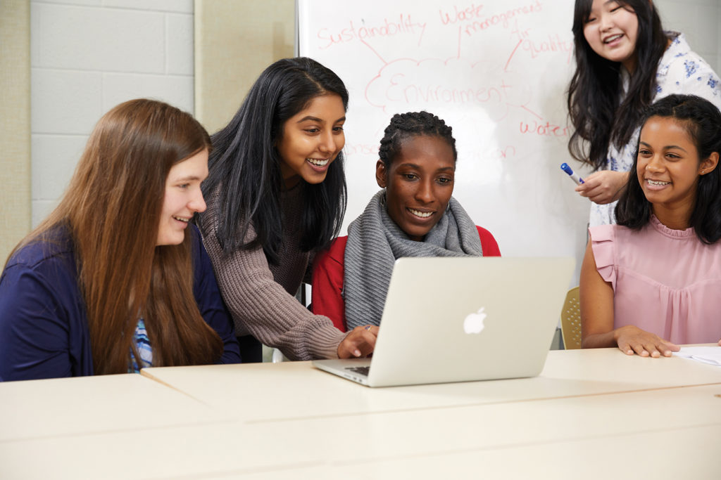Group of female students looking at shared computer.