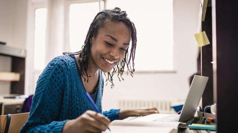 Female student studying in dorm room.