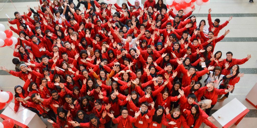 An overhead shot of a large group of students with their hands in the air.