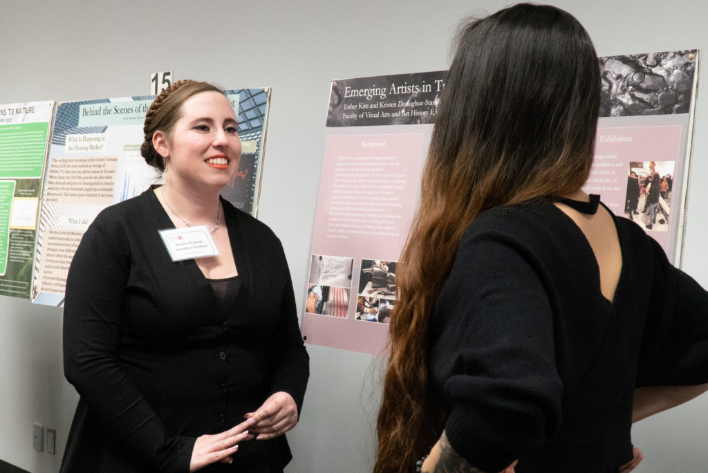 A poster presenter talking to a fellow student about their poster